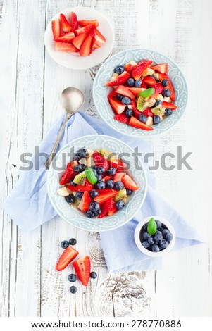 Summer salad with ripe fresh fruits and berries on rustic white wooden background, top view - stock photo
