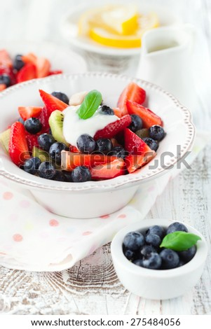 Summer salad with ripe fresh fruits and berries on white wooden background, selective focus - stock photo