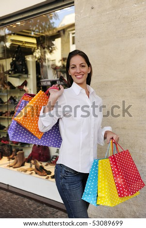 summer sale: woman with shopping bags in front of a store - stock photo