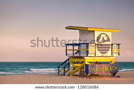 Summer scene in Miami Beach Florida, with a colorful lifeguard house in a typical Art Deco architecture, at sunset with ocean and sky in the background. - stock photo