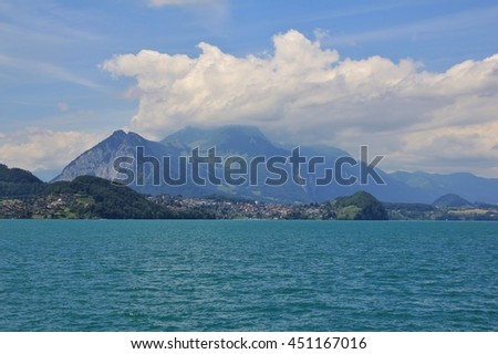 Summer scene in the Swiss Alps. Clouds creeping over the top of Mt Stockhorn. Village Spiez and turquoise lake Thunersee. - stock photo