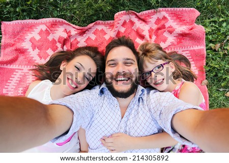 Summer scene of Happy young family taking selfies - stock photo