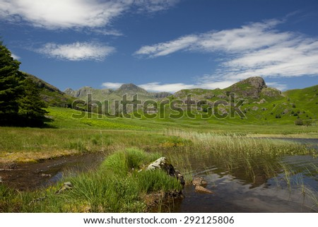 Summer scene showing a lake green grassy hills and mountains in Cumbria in northern England with blue skies  - stock photo
