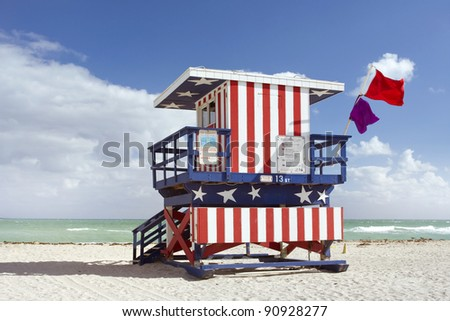 Summer scene with a lifeguard house in Miami Beach, Florida in the colors of the American flag with blue sky and ocean in the background. - stock photo