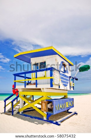 Summer scene with a typical colorful lifeguard house in Miami Beach, Florida with blue sky and ocean in the background - stock photo