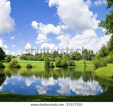 Summer scenery with lake in front, green forest on back with blue sky and clouds - stock photo