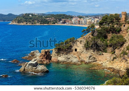 Summer sea rocky coast view with Castle of Sant Joan (Sa Caleta beach, Lloret de Mar town, Catalonia, Spain). People are unrecognizable.