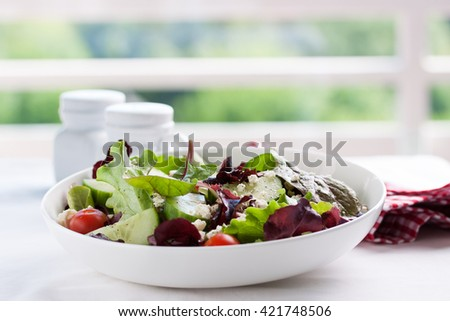 Summer season salad with salad leaves, tomatoes, cucumbers, Italian herbs and cheese in a bowl on a table, with free space for text, closeup, selective focus - stock photo