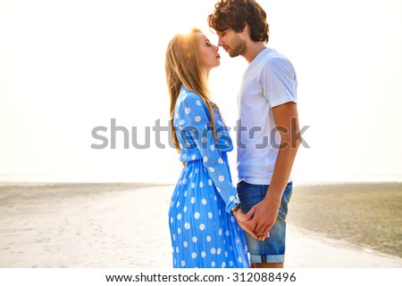 Summer sensual fashion portrait of young couple in love, having fun, relaxed end end enjoy time together at lonely exotic beach, beautiful sunset, elegant trendy clothes, romantic atmosphere. - stock photo