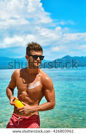 Summer Skin Care. Handsome Sexy Man In Fashionable Sunglasses Tanning Using Protective Sunscreen Lotion On Athletic Muscular Body. Male Model Sunbathing With Solar Sun Block Protection Cream On Beach - stock photo