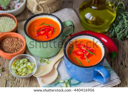 Summer soup. Spicy soup of fresh vegetables - tomatoes, peppers, garlic, thyme and spices. Additionally, flax seed, pumpkin seeds, sesame seeds.  Soft focus - stock photo