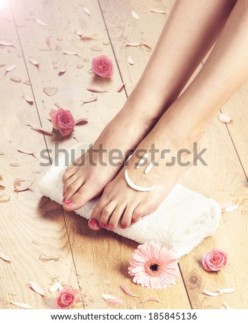 Summer spa background with a beautiful legs and flowers - stock photo