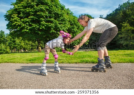 Summer sports: kid studying roller skating - stock photo