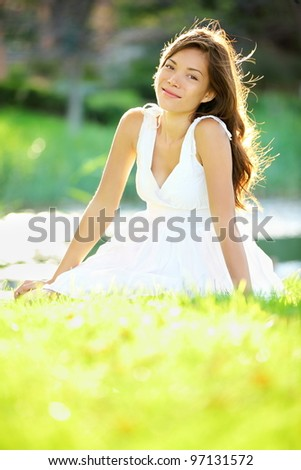 Summer / spring woman smiling happy sitting in white dress in sunny park by lake. Beautiful mixed ethnic Caucasian / Chinese Asian girl outdoor. - stock photo