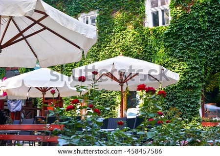 summer street cafe interior in green city park, ornate with flowers and decorative elements, white umbrella - stock photo