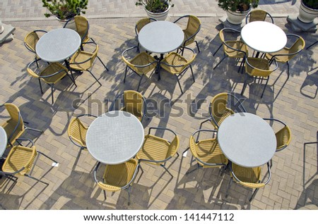 summer street cafe tables and chairs on city pavement - stock photo
