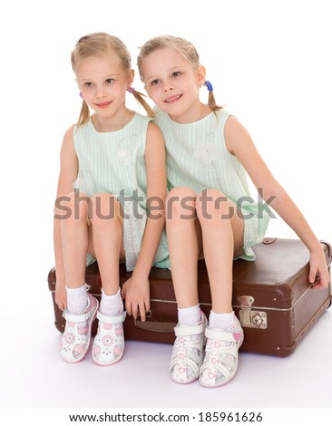 Summer, suitcase, travel, vacation, sister schastlivaye twin sisters wifunny kids with a large and very old suitcase. Isolated on white background.th a big old suitcase. Isolated on white background. - stock photo