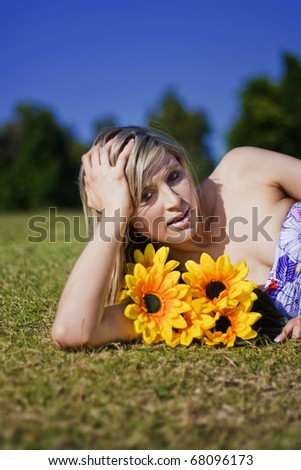Summer Sun Flowers Woman Lays With Bright Yellow Sunflowers In Her Arms In Summers Sunny Sunshine During Sunlight - stock photo