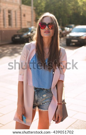 Summer sunny lifestyle fashion portrait of young stylish hipster woman walking on street,wearing cute trendy outfit,talking on phone ,smiling enjoy weekends,travel with backpack,coffee,rest,lounge
