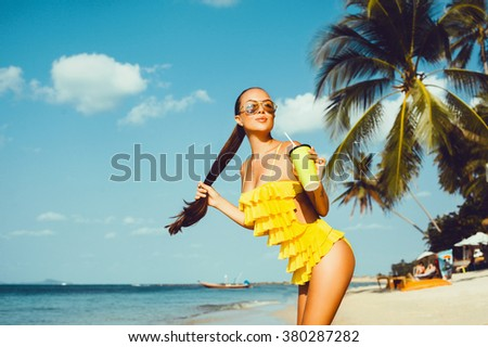 Summer sunny lifestyle outdoor portrait of young stylish bikini woman, young girl posing in the beach drinking tasty cocktail,smiling enjoy her weekends,Yellow detox cleanse vegetable smoothie Healthy - stock photo