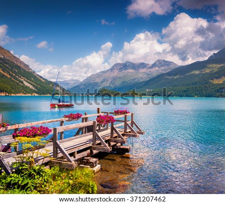 Summer sunny scene on the Silsersee lake with yacht and blooming flowers. District of Maloja, Swiss canton of Graubunden, Switzerland, Alps, Europe.  - stock photo