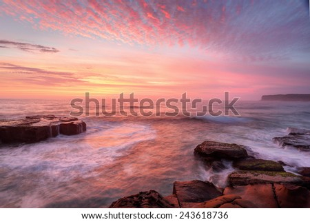 Summer sunrise skies  light up with colour throwing warmth across the  landscape and whitewater seas wash around the rocks at North Avoca Central Coast NSW Australia - stock photo