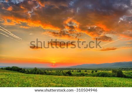 Summer sunset in the fields, orange sky - stock photo