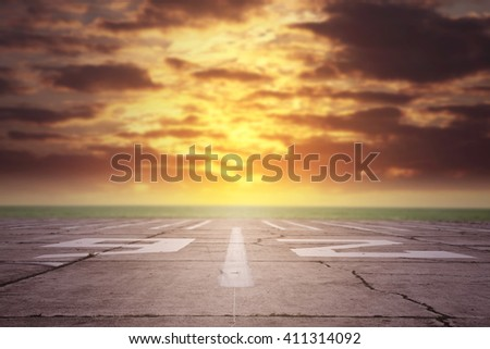 summer sunset time and white marks on gray background of runway and dark sunset time  - stock photo