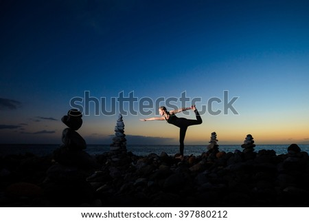 Summer sunset yoga session on beautiful Playa del Duque beach with stone pile stacks silhouettes - tropical Tenerife island, Canary in Spain. Warrior pose - Virabhadrasana - stock photo