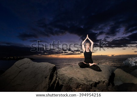 Summer sunset yoga session on beautiful Playa Fanabe beach - tropical Tenerife island, Canary in Spain. Meditation - lotus pose - padma asana