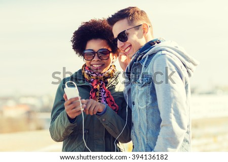 summer, technology, people and friendship concept - smiling couple with smartphone and earphones listening to music on city street - stock photo