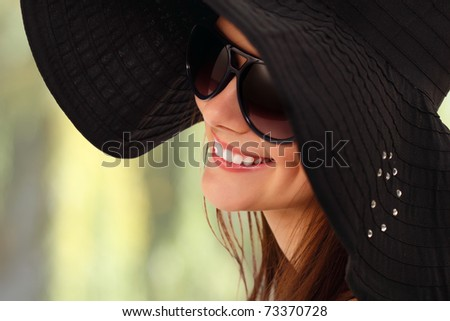 summer teen girl cheerful in panama and  sunglasses enjoying over green nature background