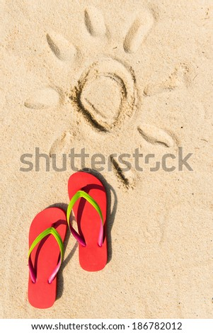 Summer theme with red flip flop on sandy beach - stock photo