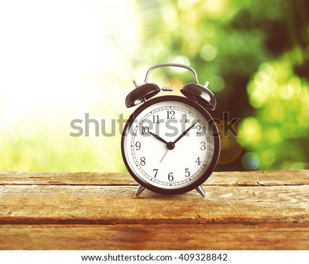 Summer time concept. Alarm clock on wooden table on green background - stock photo