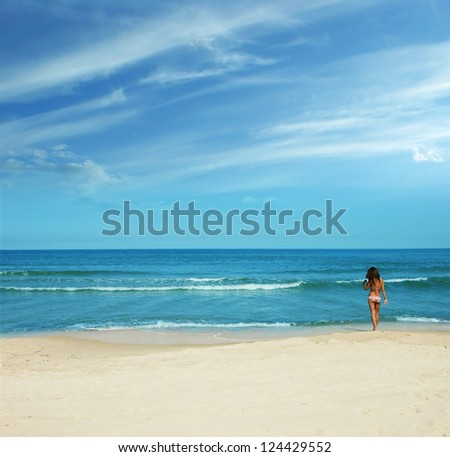 summer time on the beach - slim sunburnt brunette going to the sea - stock photo