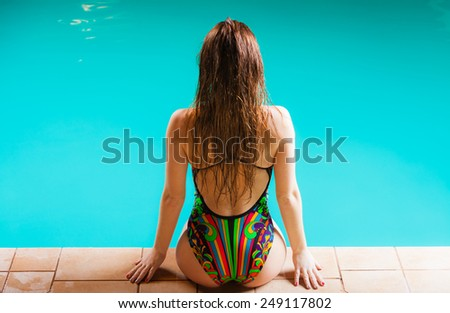 Summer time, relax and vacation concept. Sensual woman buttocks in swimsuit back view. Beautiful fit female body, girl sitting at poolside. - stock photo