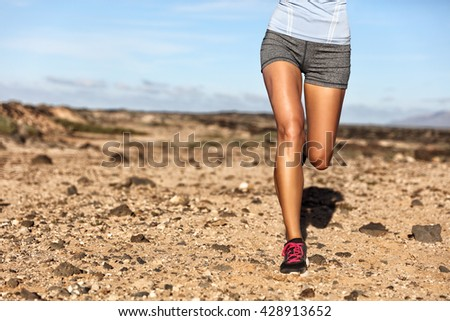 Summer trail running athlete runner legs lower body crop. Fitness woman jogging living an active lifestyle jogging on rocky path in mountain nature landscape. Shoes, knees, thighs weight loss concept. - stock photo