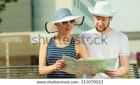 Summer travel concept. Young tourist couple on vacation sitting on city bench looking up directions on map - stock photo