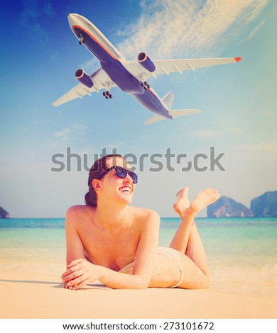 summer travel. young woman is lying on beach with aeroplane flying above - stock photo