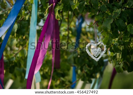 Summer tree in blue and violet blossom with wedding decoration - ribbons hearts - stock photo