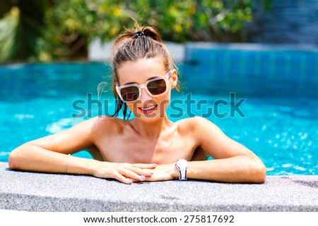 Summer trendy close up fashion portrait of sexy tanned woman relaxed and swimming at pool. wearing bright bikini and sunglasses, smiling and looking on camera. positive mood. - stock photo