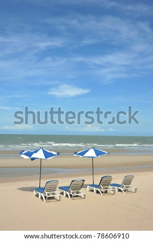 summer tropical beach with blue sky with umbrella and chair - stock photo