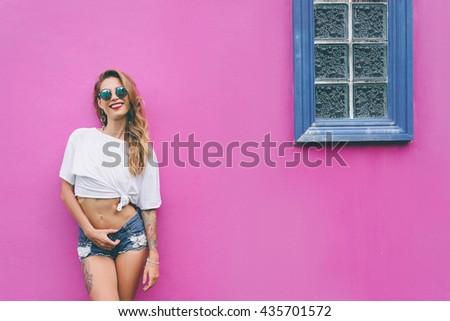 Summer urban fashion. Fun and colorful. Young pretty happy woman in shorts posing against pink wall. - stock photo