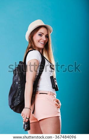 Summer vacation and tourism concept. Young woman in straw hat with backpack camera on blue sideview
