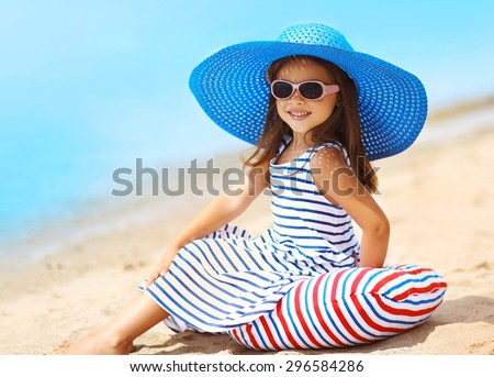Summer, vacation and travel concept - portrait of pretty little smiling girl in a striped dress and straw hat relaxing resting on the beach near sea - stock photo