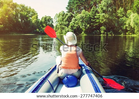 Summer vacation - Back view of young woman kayaking on river. Vintage toning - stock photo
