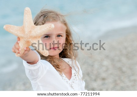 Summer vacation - beautiful girl with starfish at the beach - stock photo