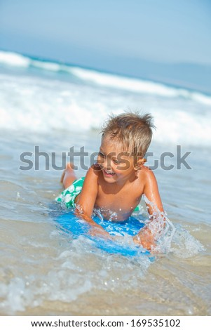Summer vacation - Boy has fun on the surfboard in transparency sea - stock photo