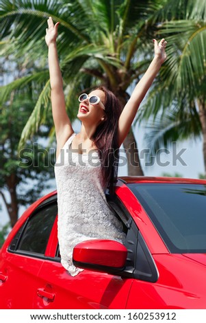 Summer vacation car road trip freedom concept. Happy woman cheering joyful during holiday travel in red car. - stock photo
