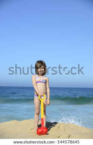 summer vacation child with showel on the beach